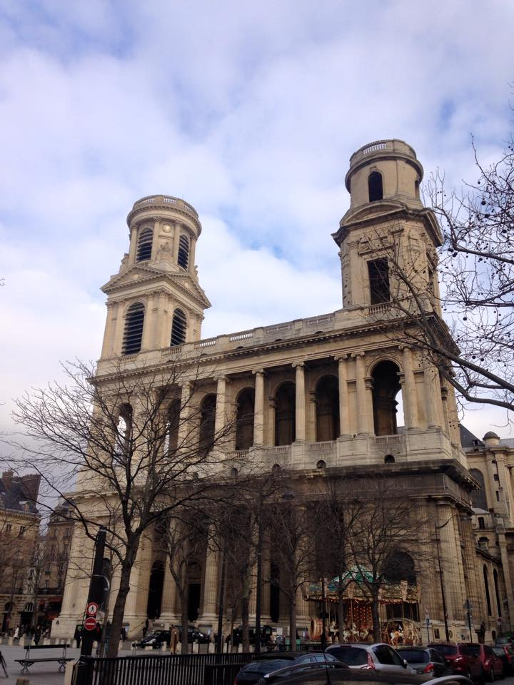 This is an exterior picture of a tall double towered building.