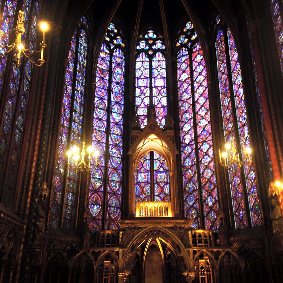 This is an interior picture of a space that has many stained glass windows.