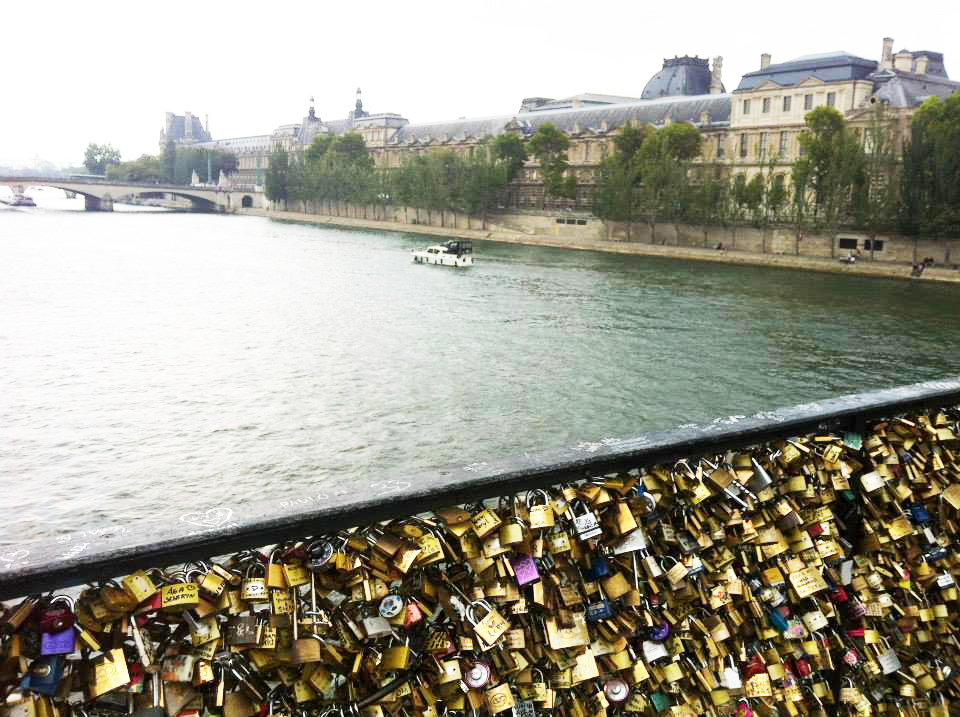 A fence with many locks over a river.