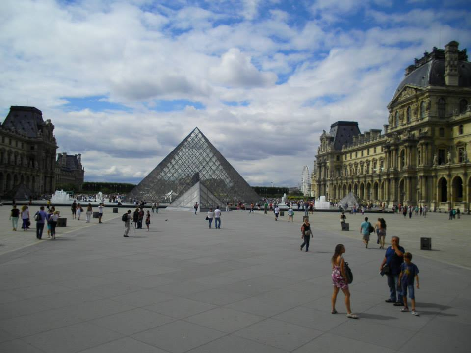 There are many people standing, walking, and sitting at the exterior of Louvre Museum.