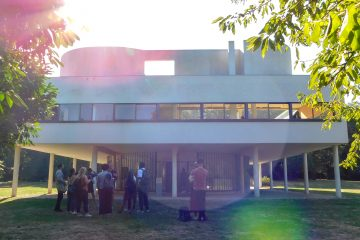 People are gathering near the rear facade and venturing inside of the Villa Savoye.