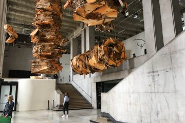 People are experiencing the interior space and suspended sculptures of the Palais de Tokyo.