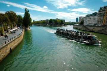 This is a picture of the River Seine. There is a boat that is crowded on the river.