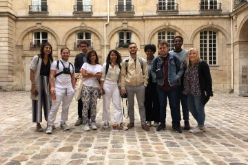There are people standing and posing for a picture in the Paris Center courtyard.