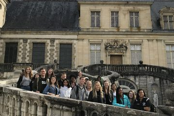 People standing and posing on the Grand Staircase of the Fontainebleau.