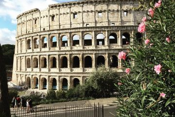 People are walking and standing near the exterior of the Colosseum.