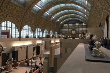 The multi-story interior of Musee D'Orsay . This room has sculptures and people on both levels.