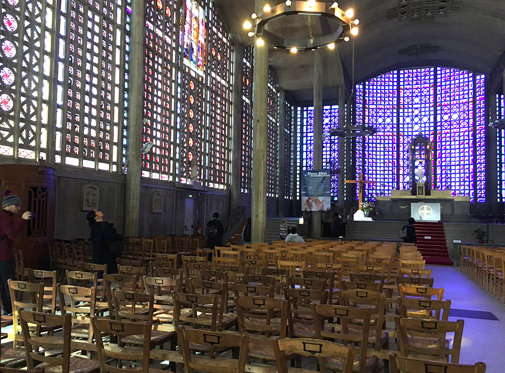 People wander and sit in the interior of Notre Dame de Raincy.