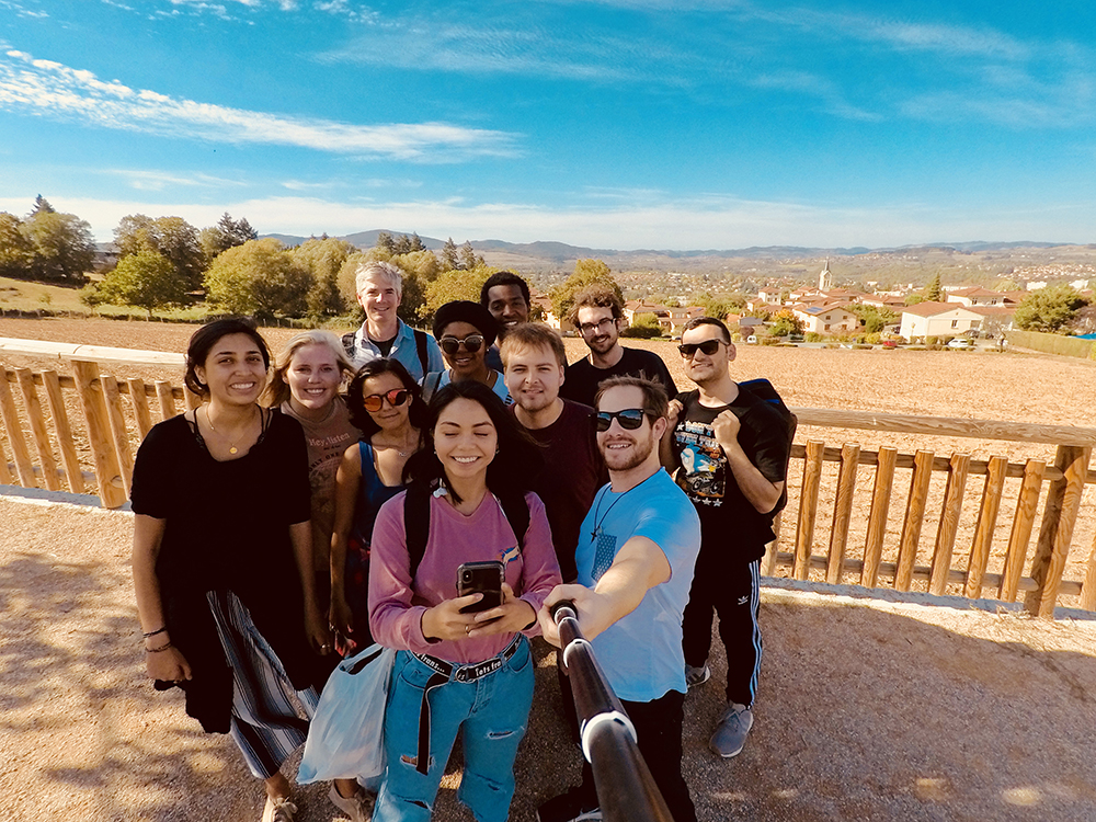 10 students take a selfie with Professor Holton with the city in the background.