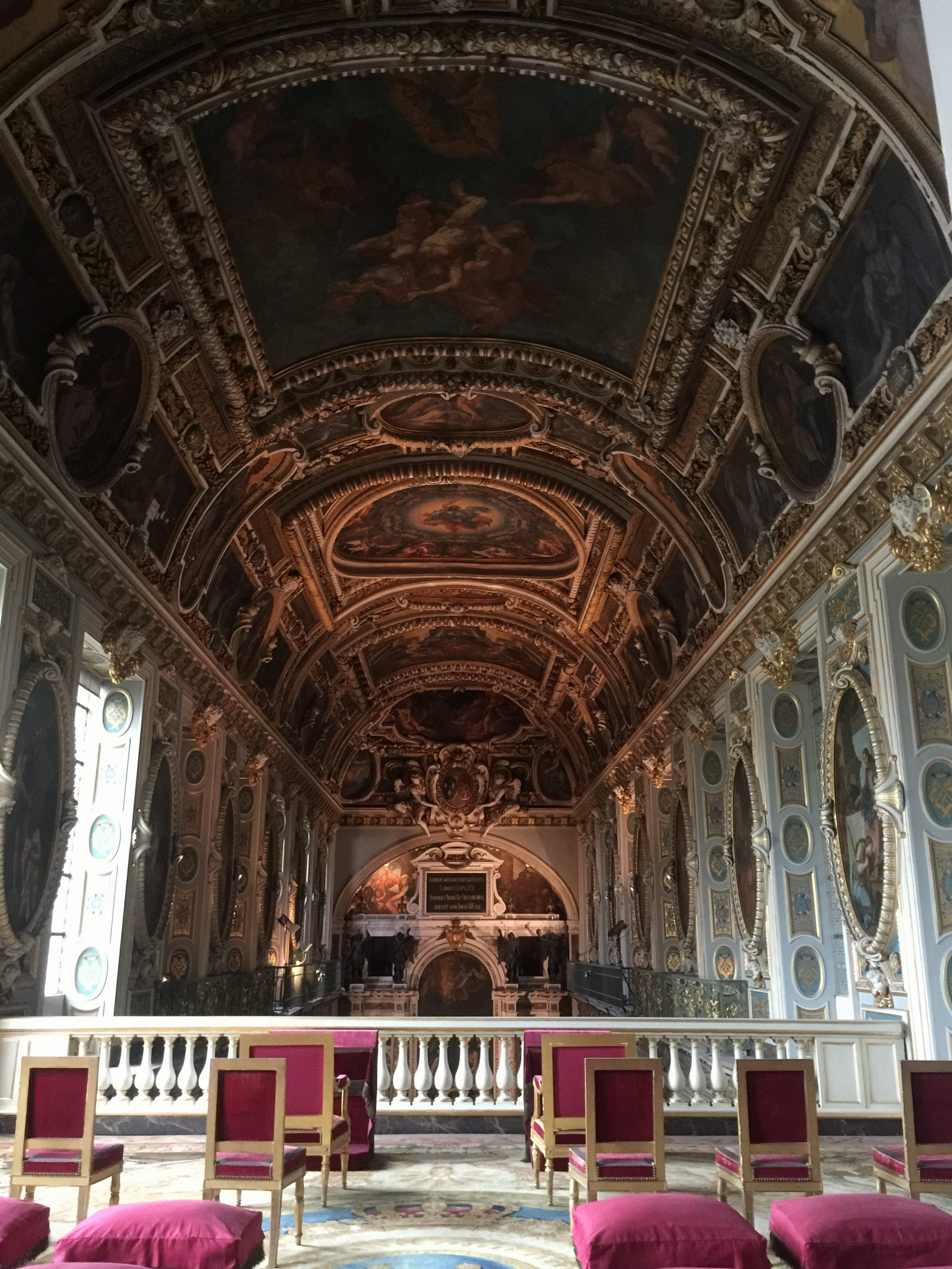 The ceiling murals are seen at the upper level of the chapel of the Palace of Fontainebleau.