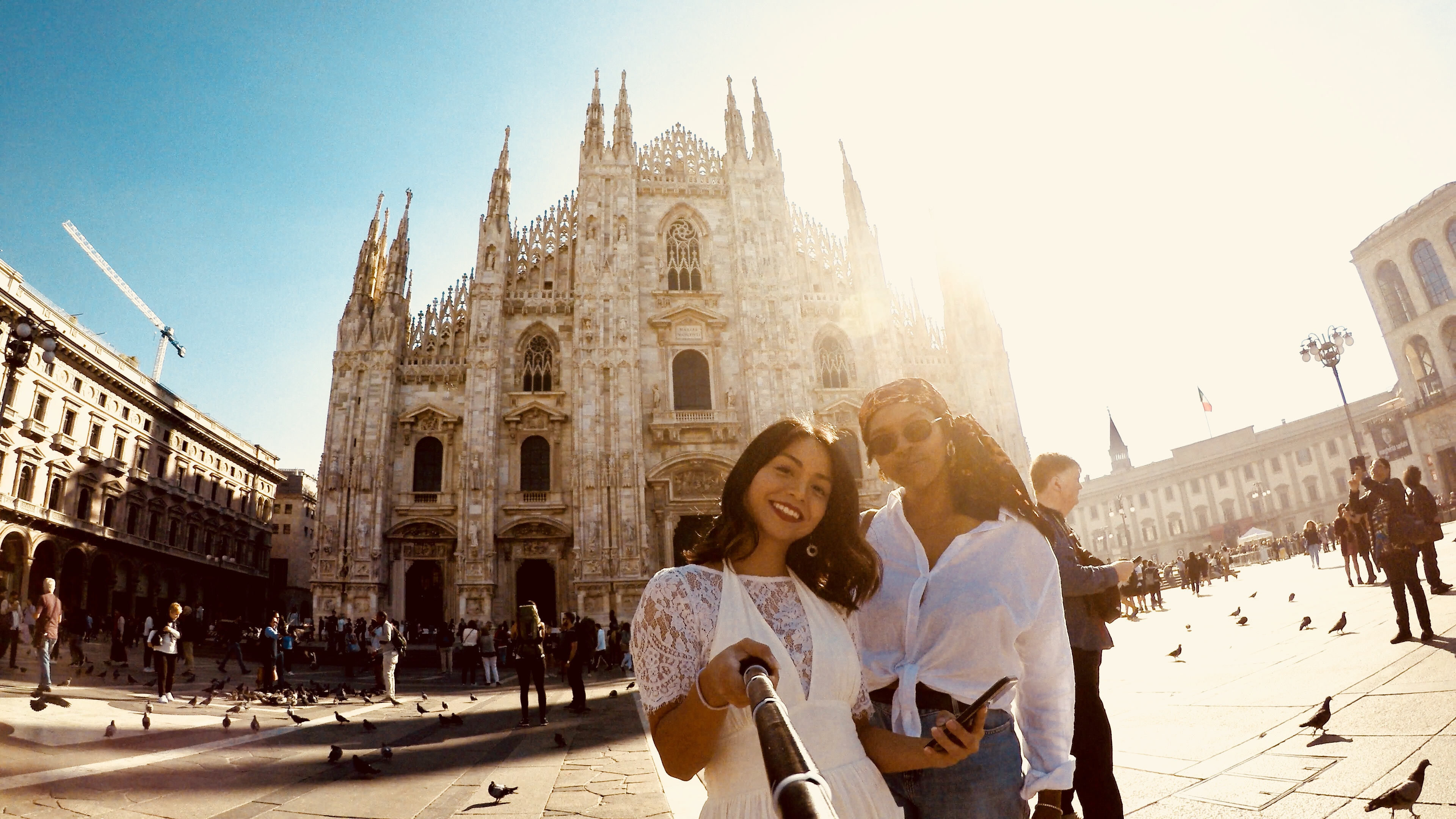 Two people take a selfie in front of Milan Duomo.