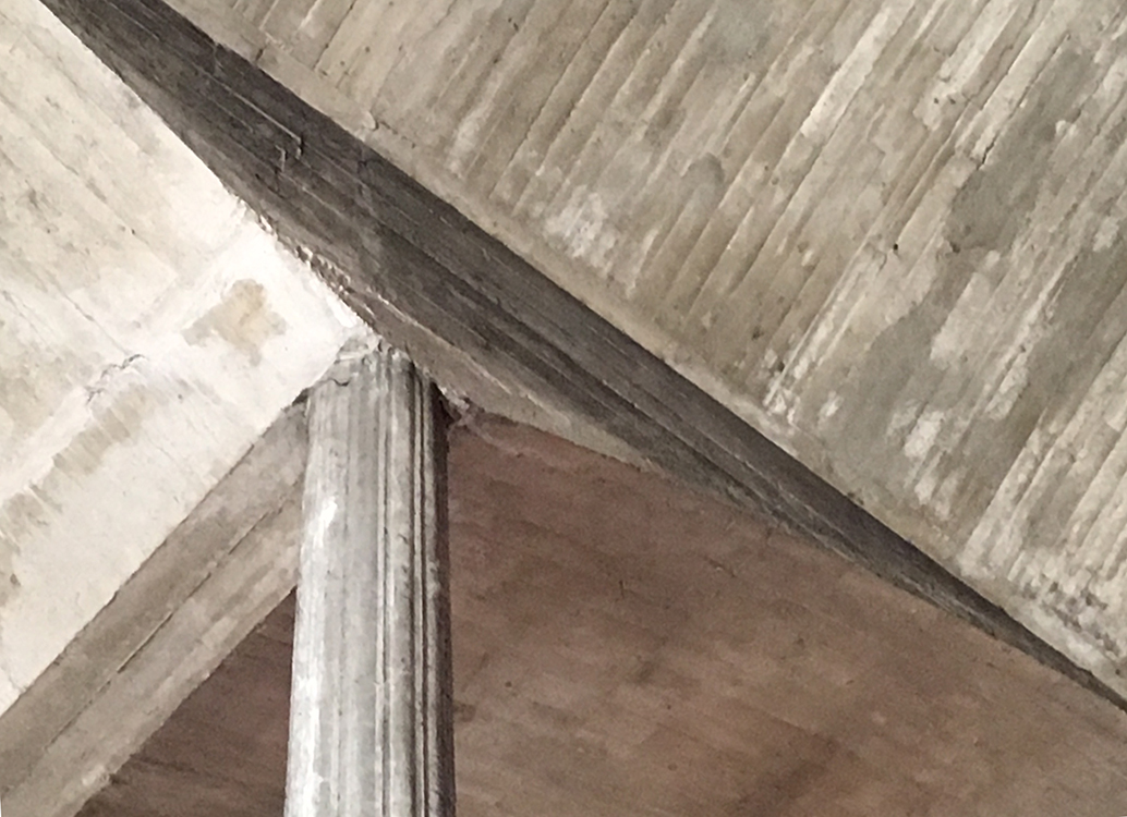 A detail image of a column/beam/roof connection that shows the striations of the formwork.