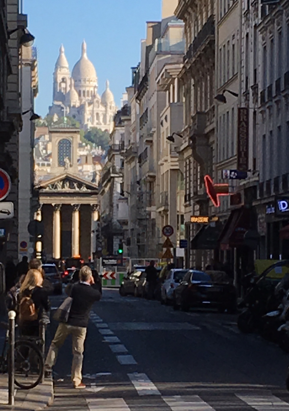 The Sacré-Couer can be seen in between a civilian populated street lined with tall buildings.