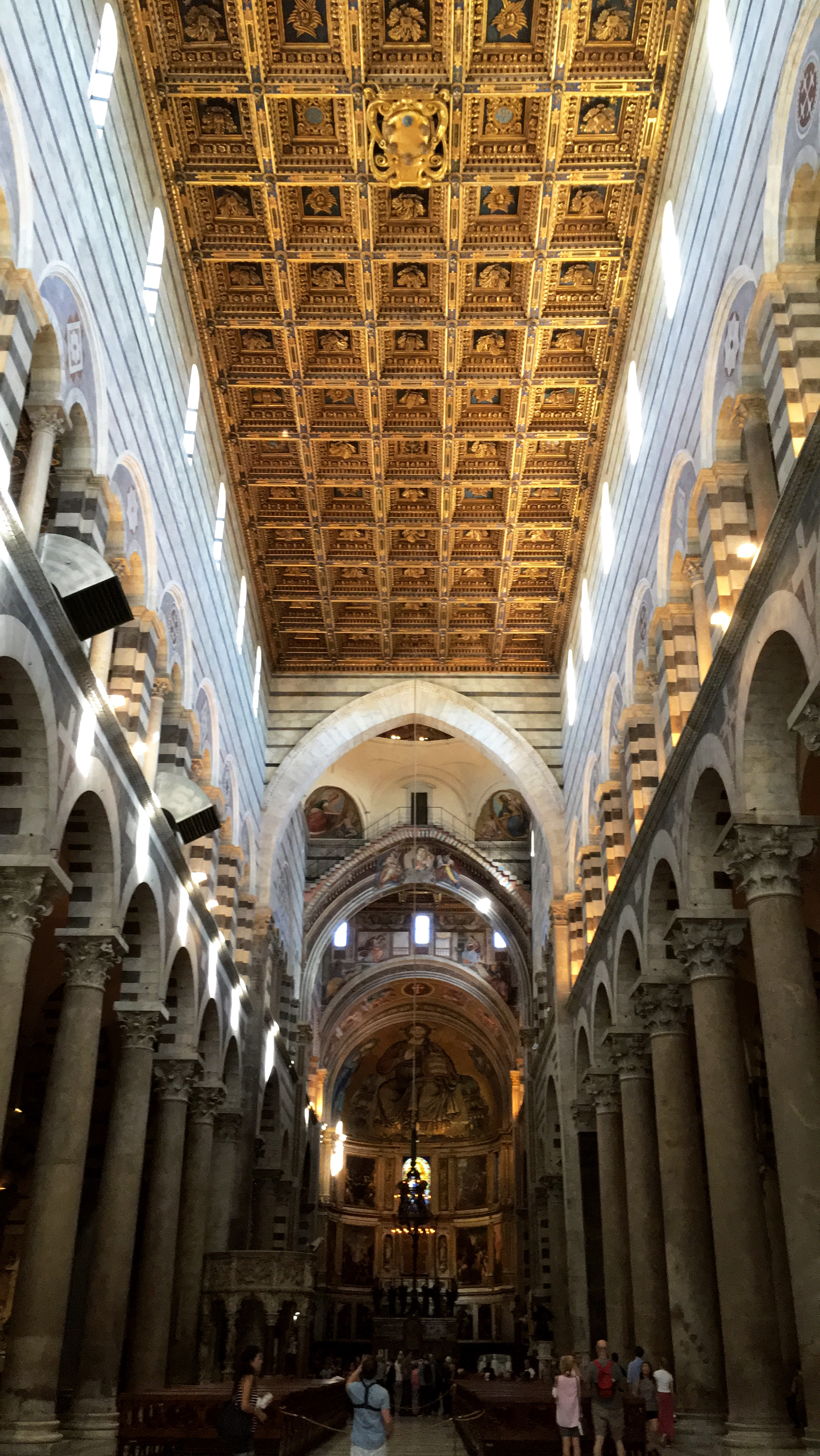 People are standing, walking, and taking pictures in the interior space of the Pisa Cathedral.