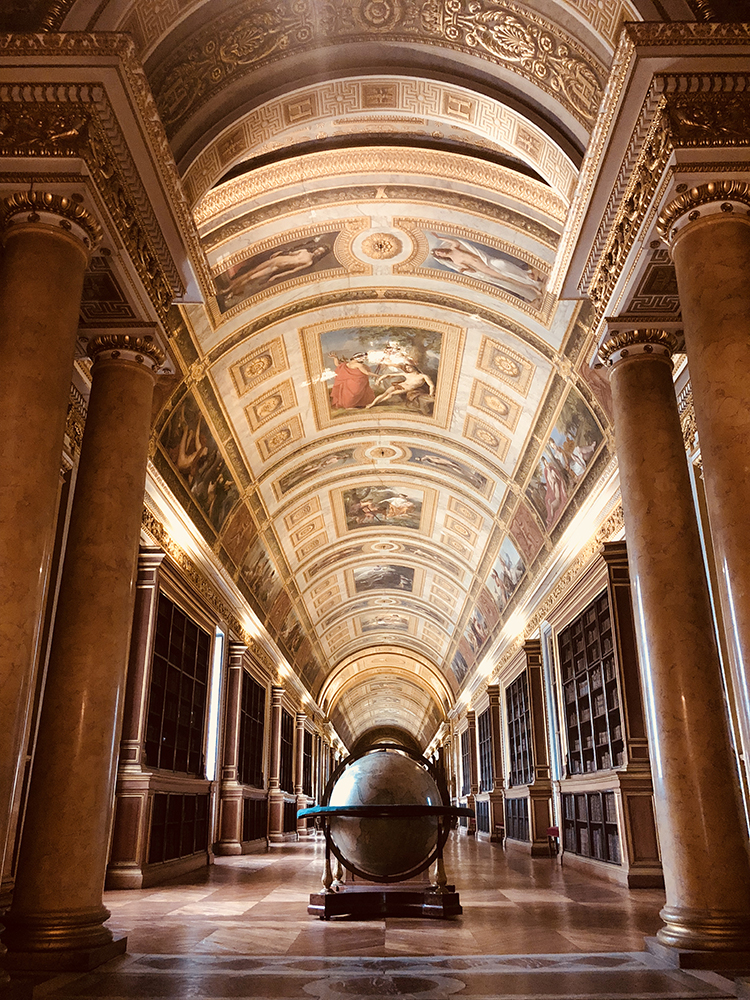 The Palace of Fontainebleau Library has ceiling murals, columns, bookshelves, and an ornamental globe.