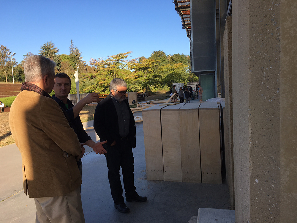Dean Tsolakis and Director Ghandour learning about a subject on the side of a structure.
