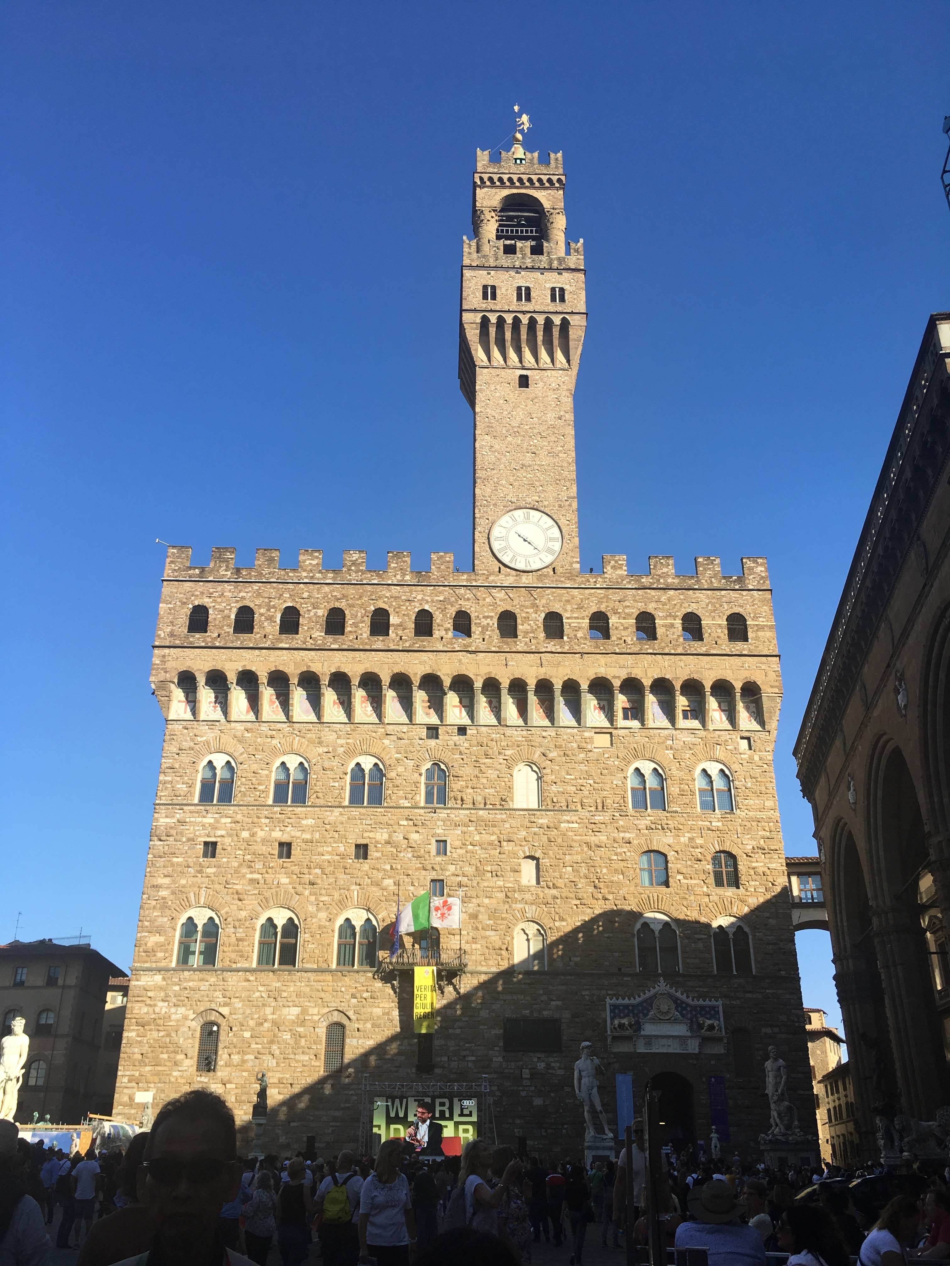 A picture of the Palazzo Vecchio. There are many people crowded in the area in front of it.