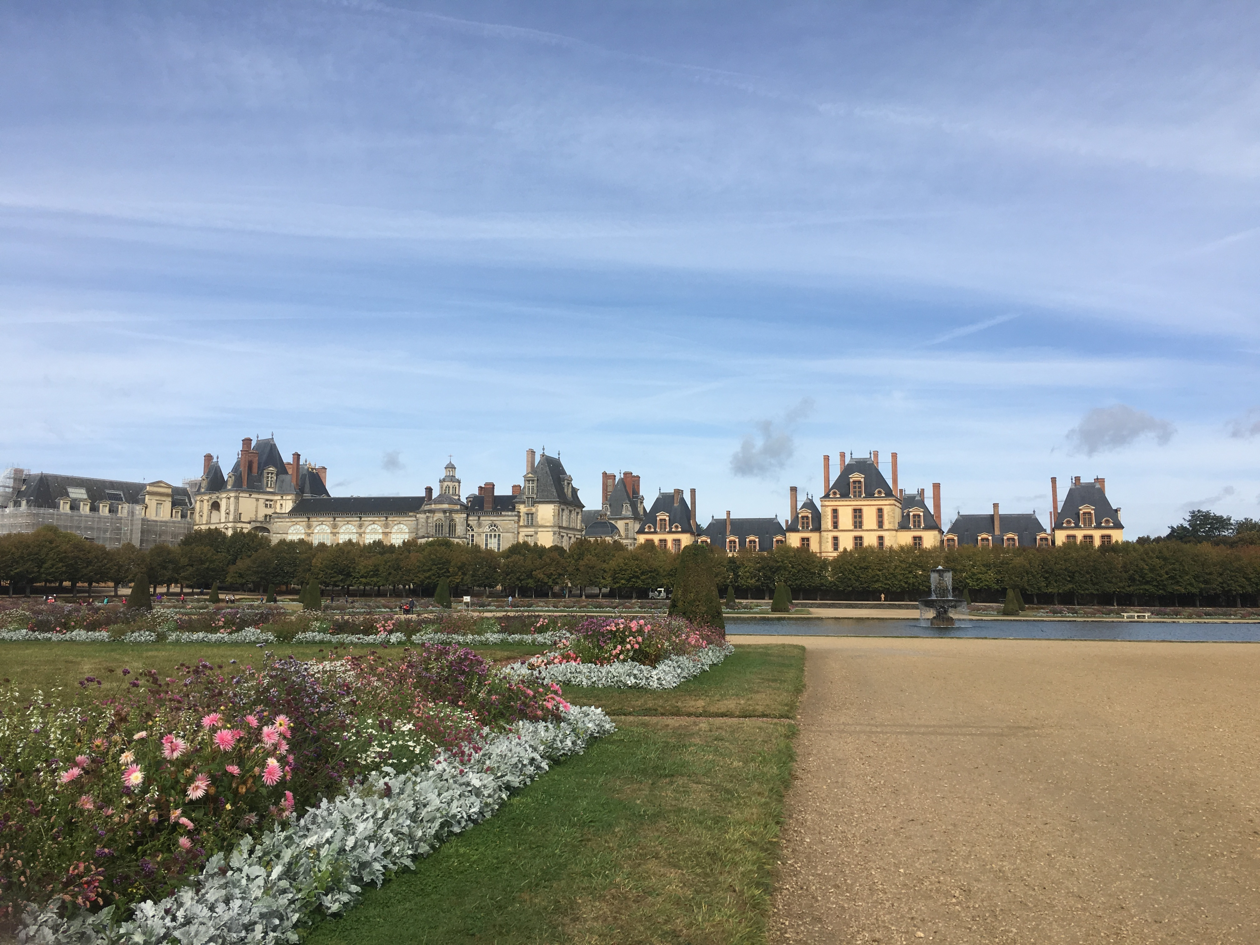 This a view of the Palace from the gardens which also shows a waterway and vegetation with flowers.