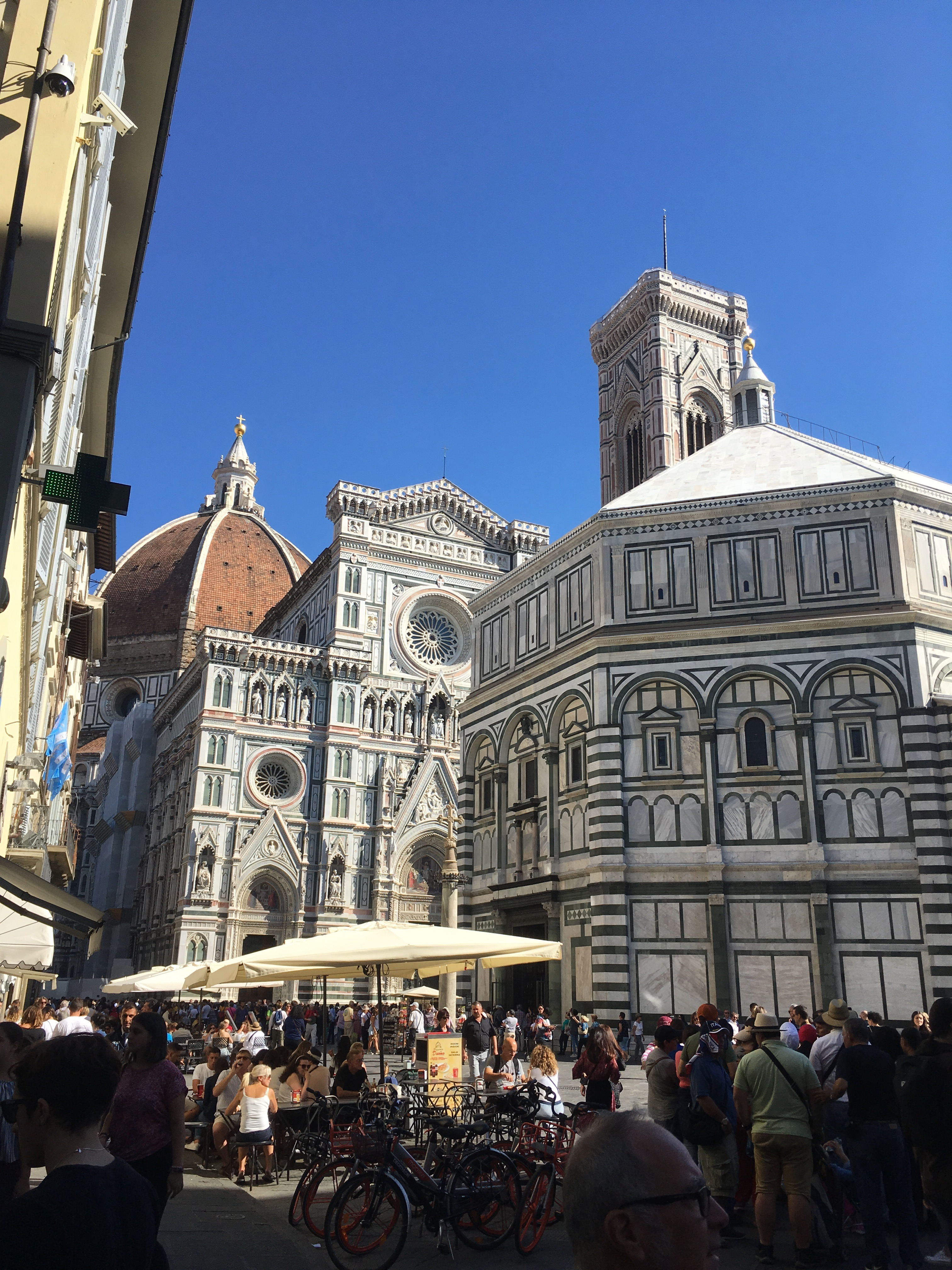Many people are sitting, standing, and walking outside of the Piazza del Duomo.