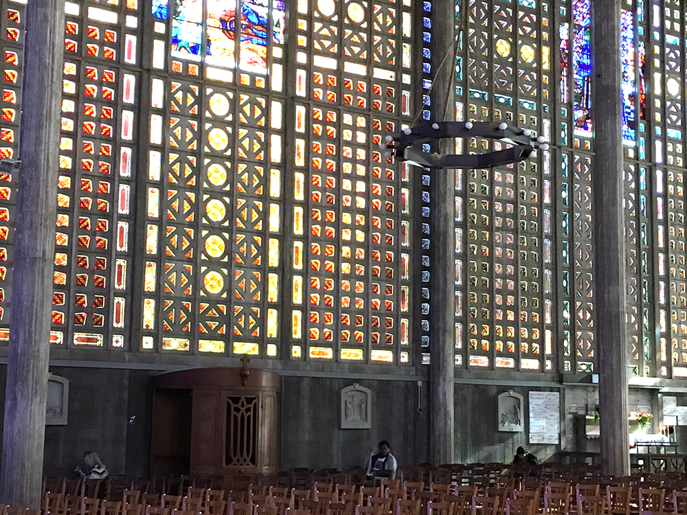 A space with many stained glass windows with people sitting in chairs.