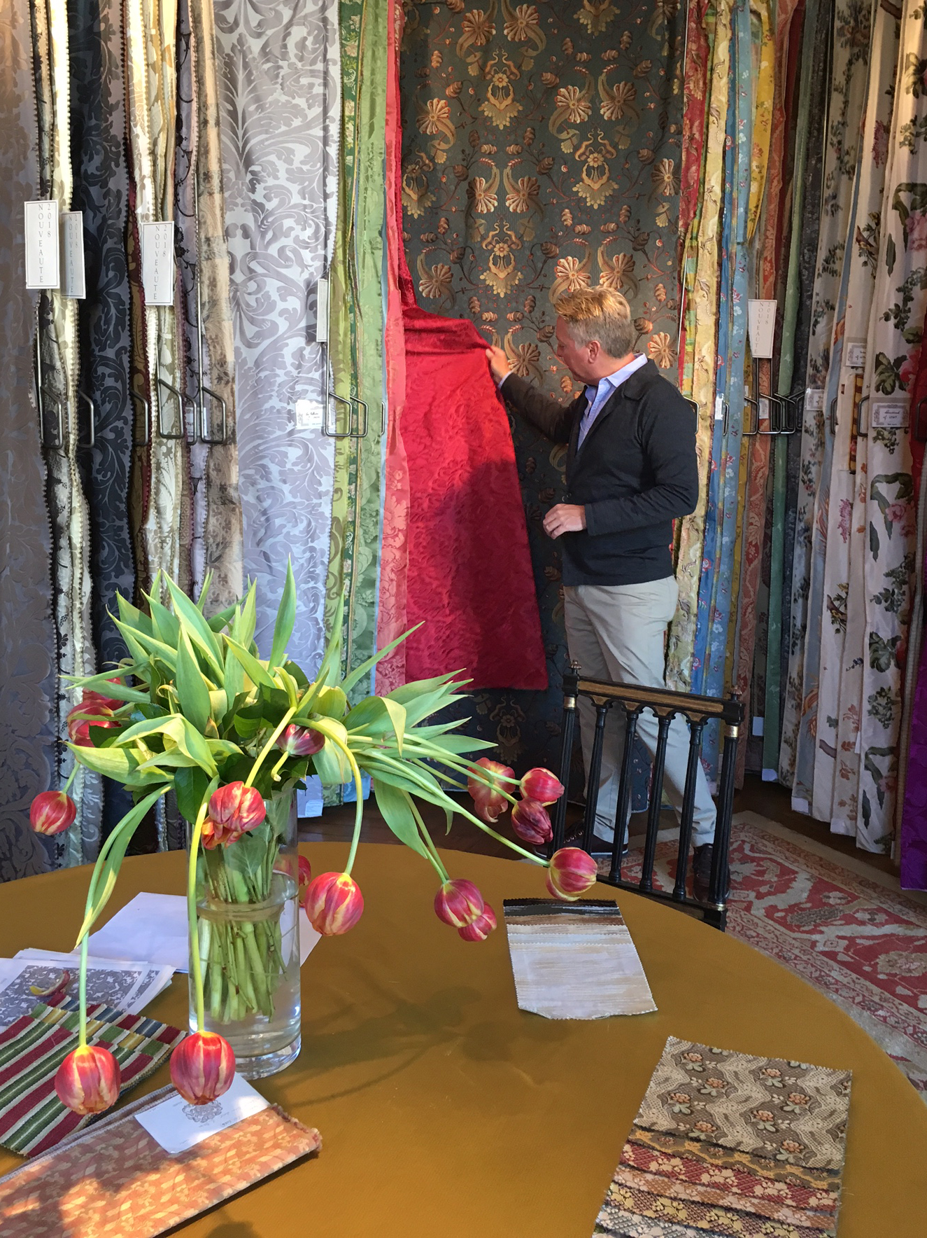 Interior of Prelle. Man looking at very colorful fabrics hanging straight down.