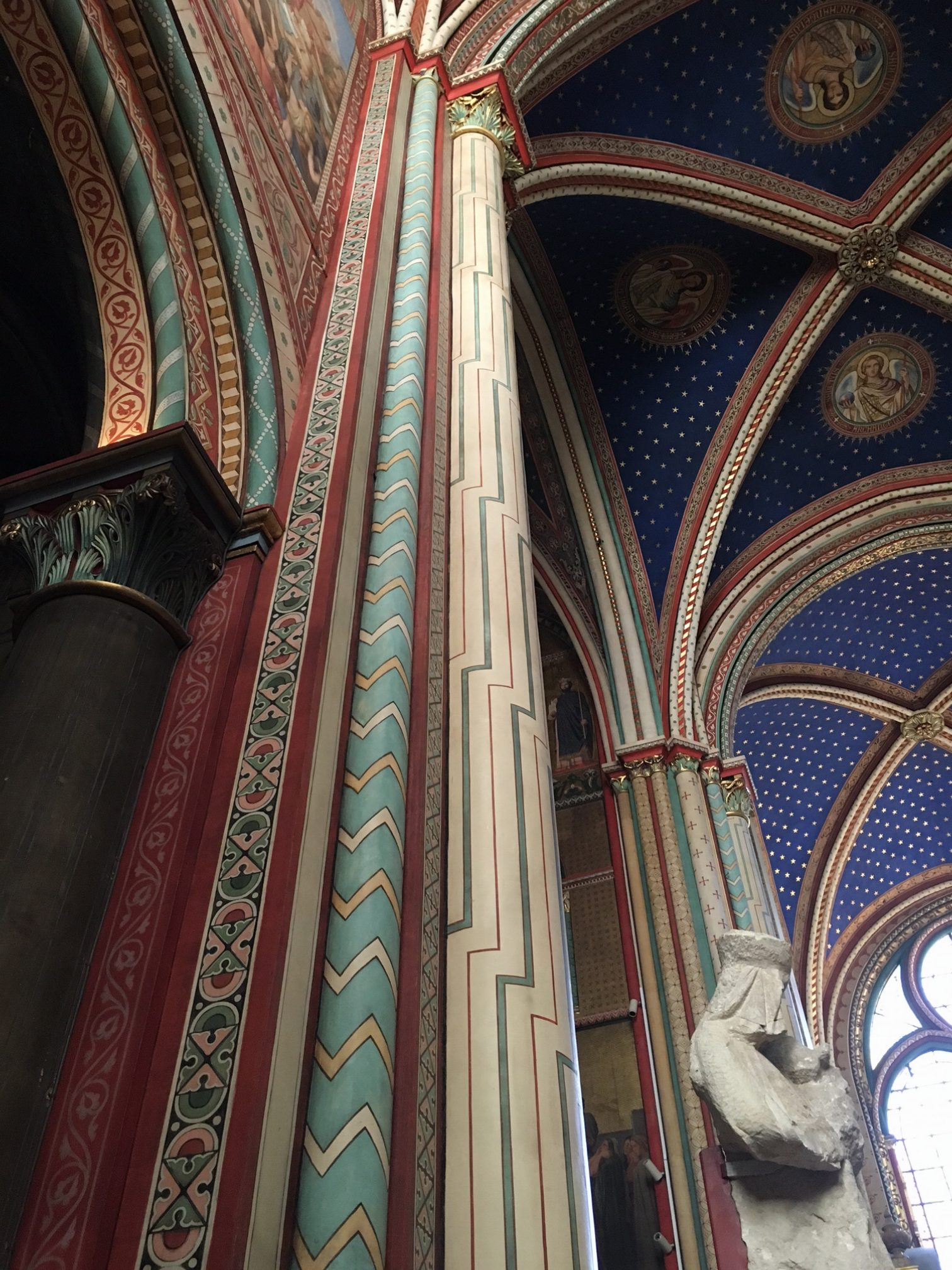 The interior of Eglise Sain Germain. The colorful columns rise into vaulted ceilings.