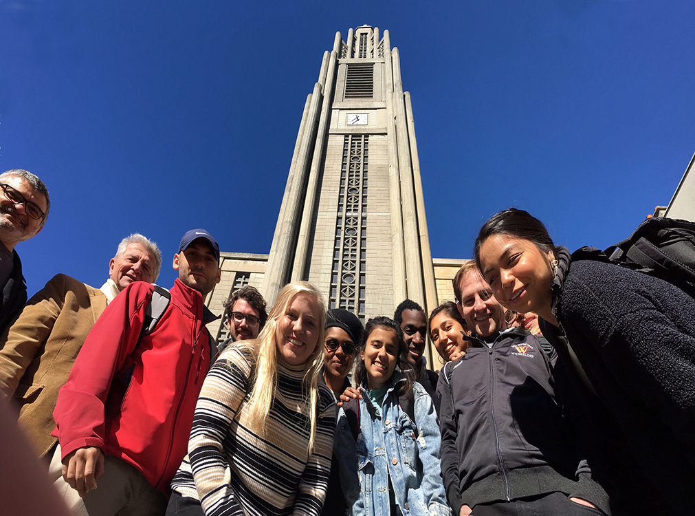 A group of people taking a ground up angled picture in front of a tower that has a clock.