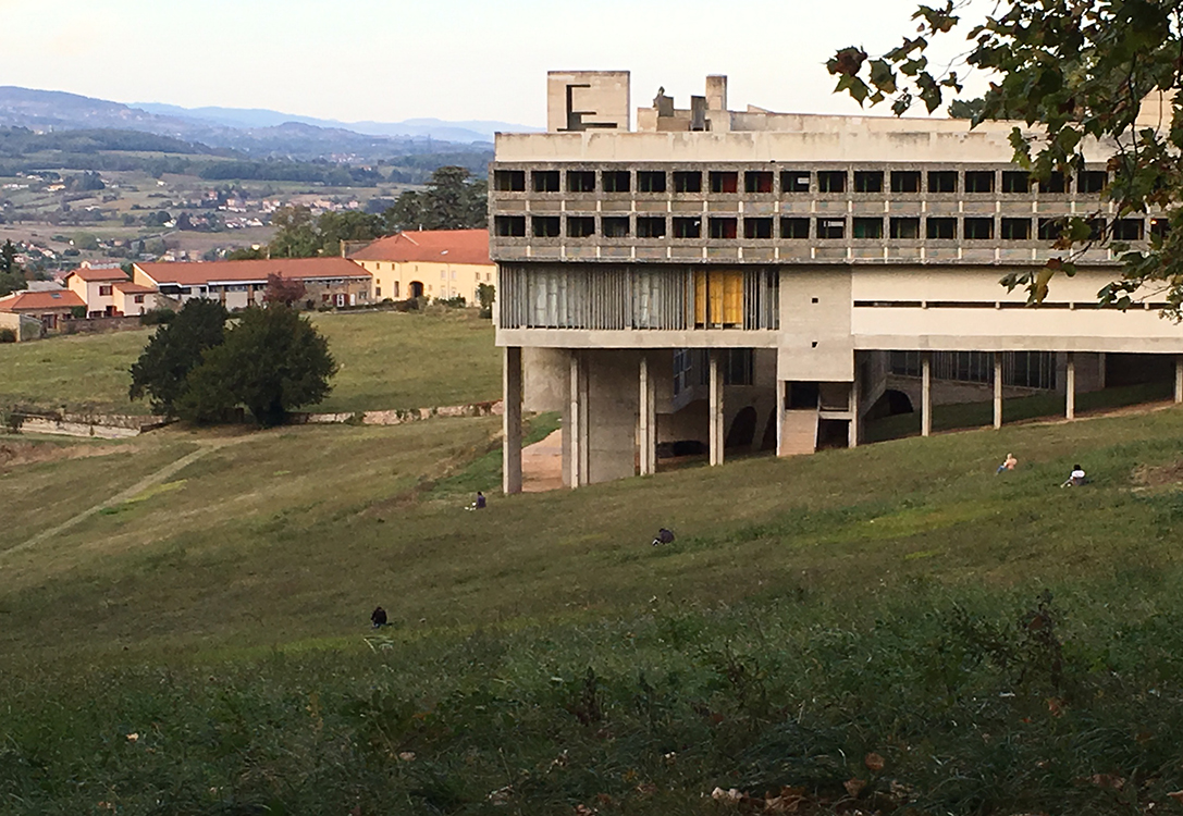 Exterior view of the building. People are sitting along the hillside.