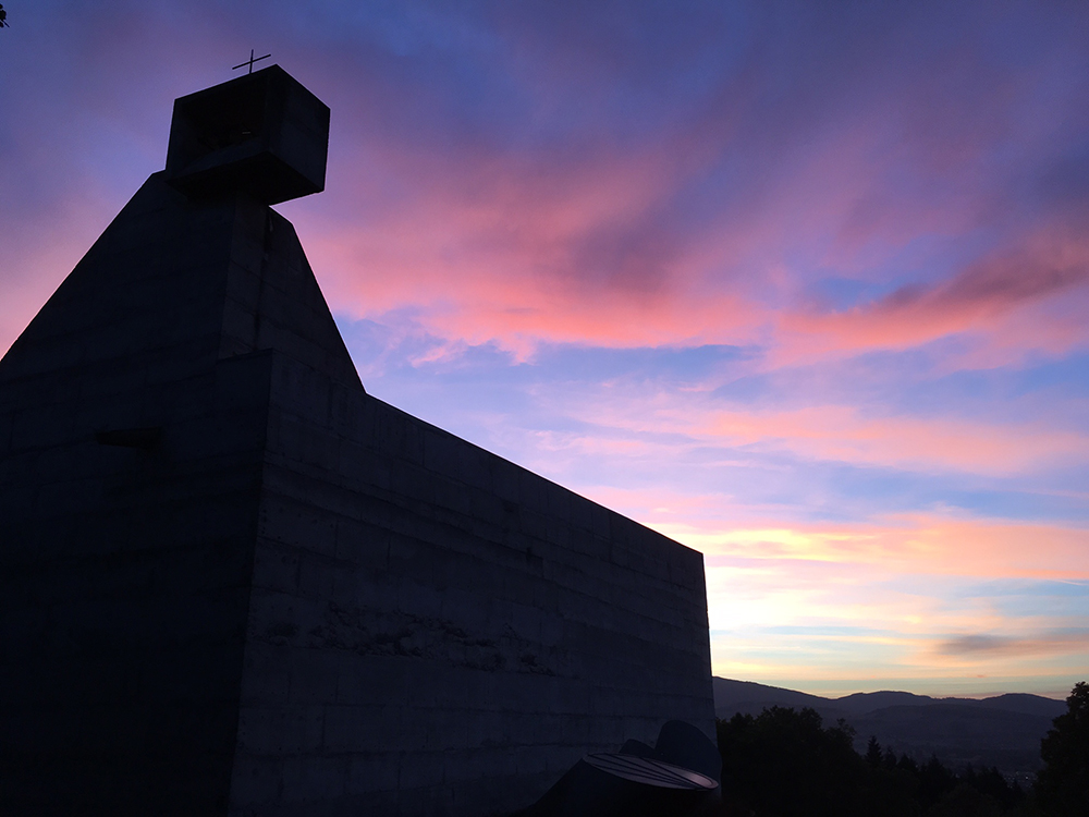 A silhouette of the exterior of the church at the vacancy of light on the site.