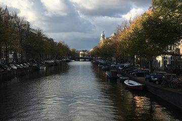 A picture of an Amsterdam canal. There are many boats in the canal.