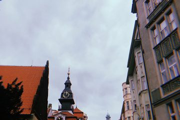 A clock tower in Prague. The clock tower is surrounded by tan buildings.