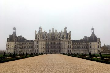 A light brown gravel path leading to the Royal Chateau de Chambord from the gardens.