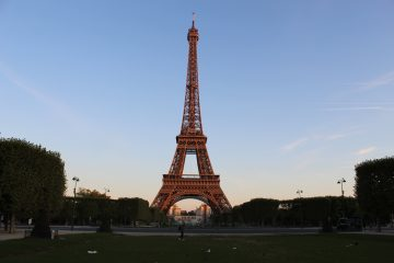 A picture of the Eiffel tower with the sunrise glow on it.