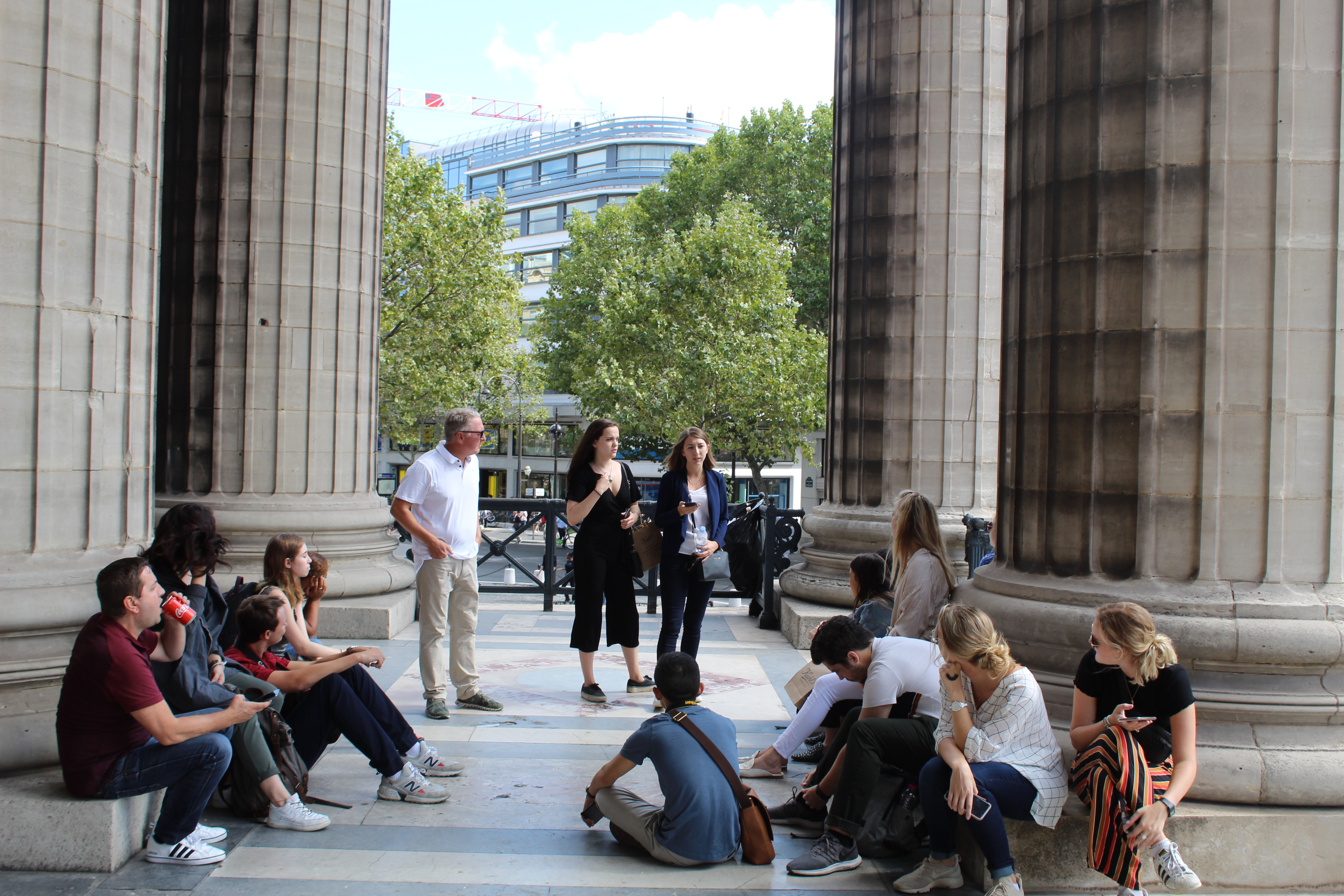 Group of people sitting on the bases of columns, and 3 people standing.