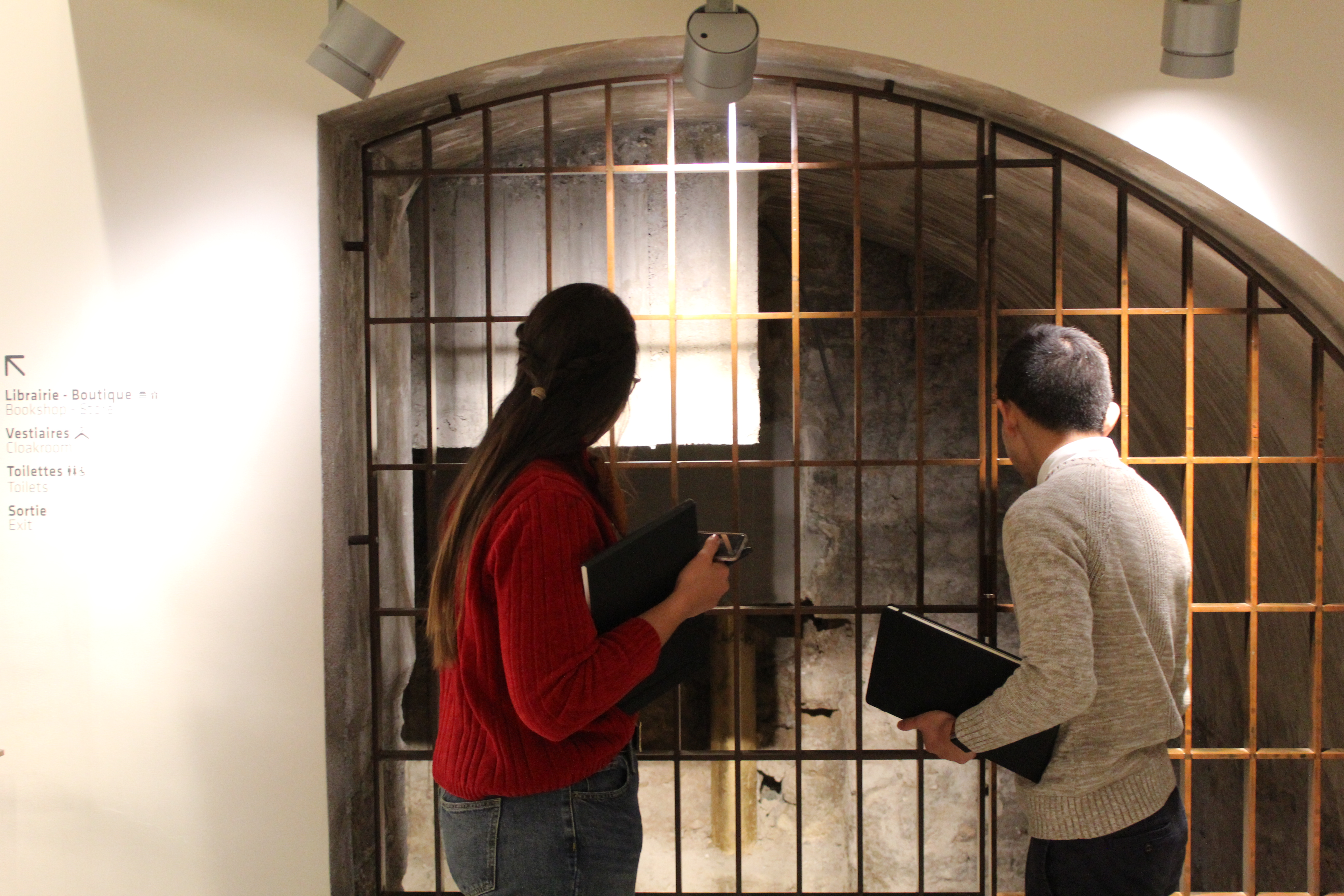 Two people looking through bars of a cage door.