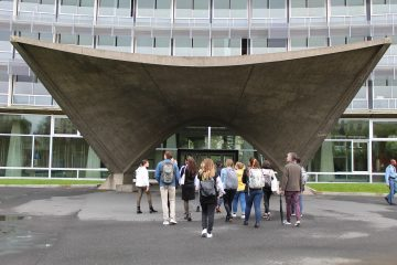 Group of people walking toward a concrete pavilion in front of a glass building.