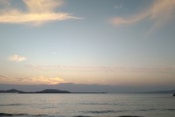 Picture of a body of water at sunset with islands in the background. Colored smoke is in the sky.