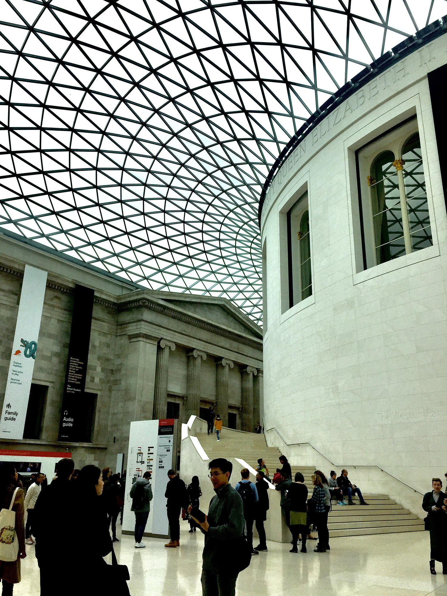 People are walking and standing in a space inside a museum. There is an intricately designed roof.