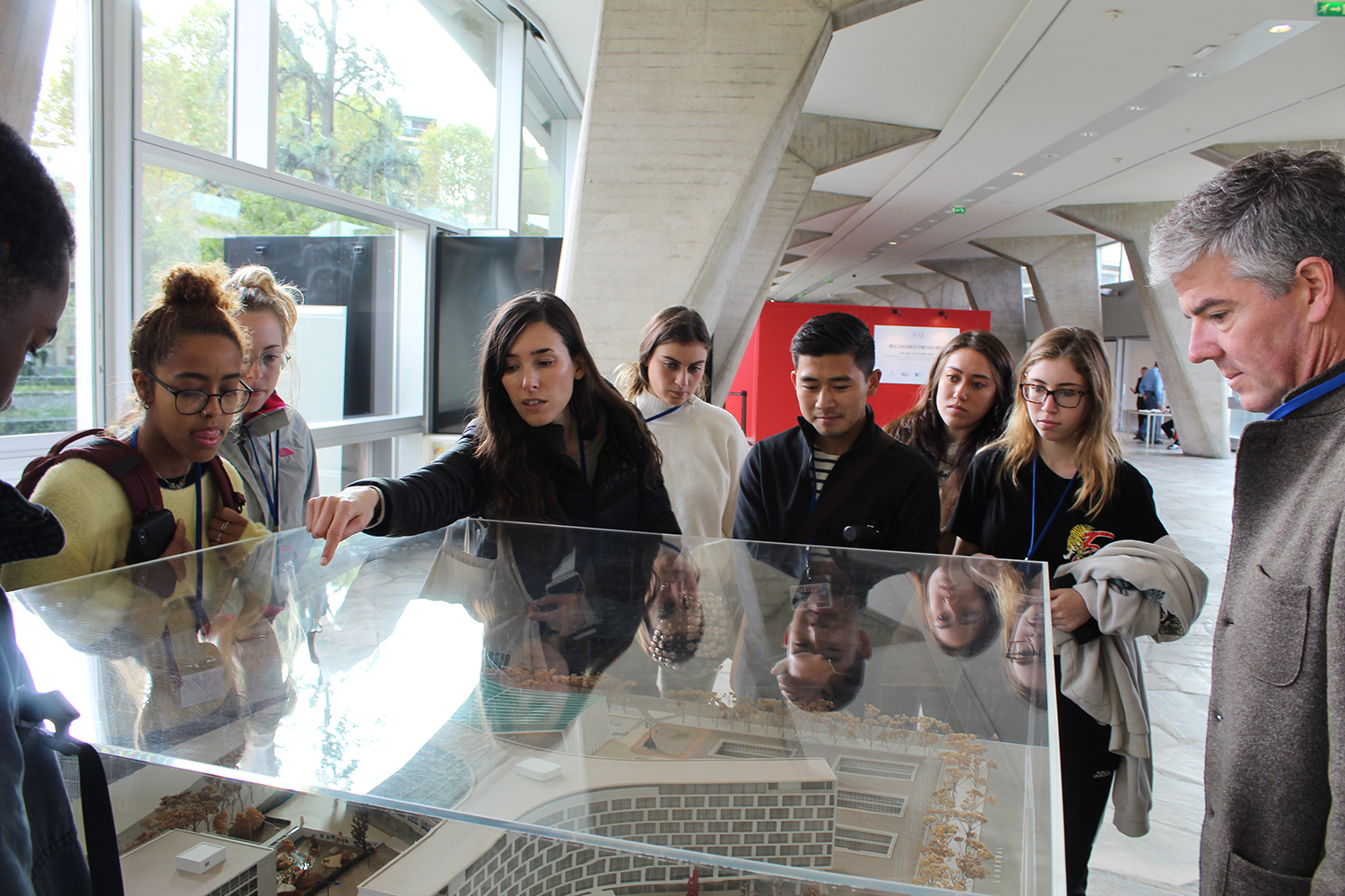 A group of people looking at a model inside a glass case.