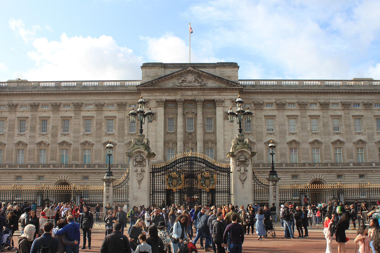 Many people are walking, standing, and taking pictures in front of a palace.