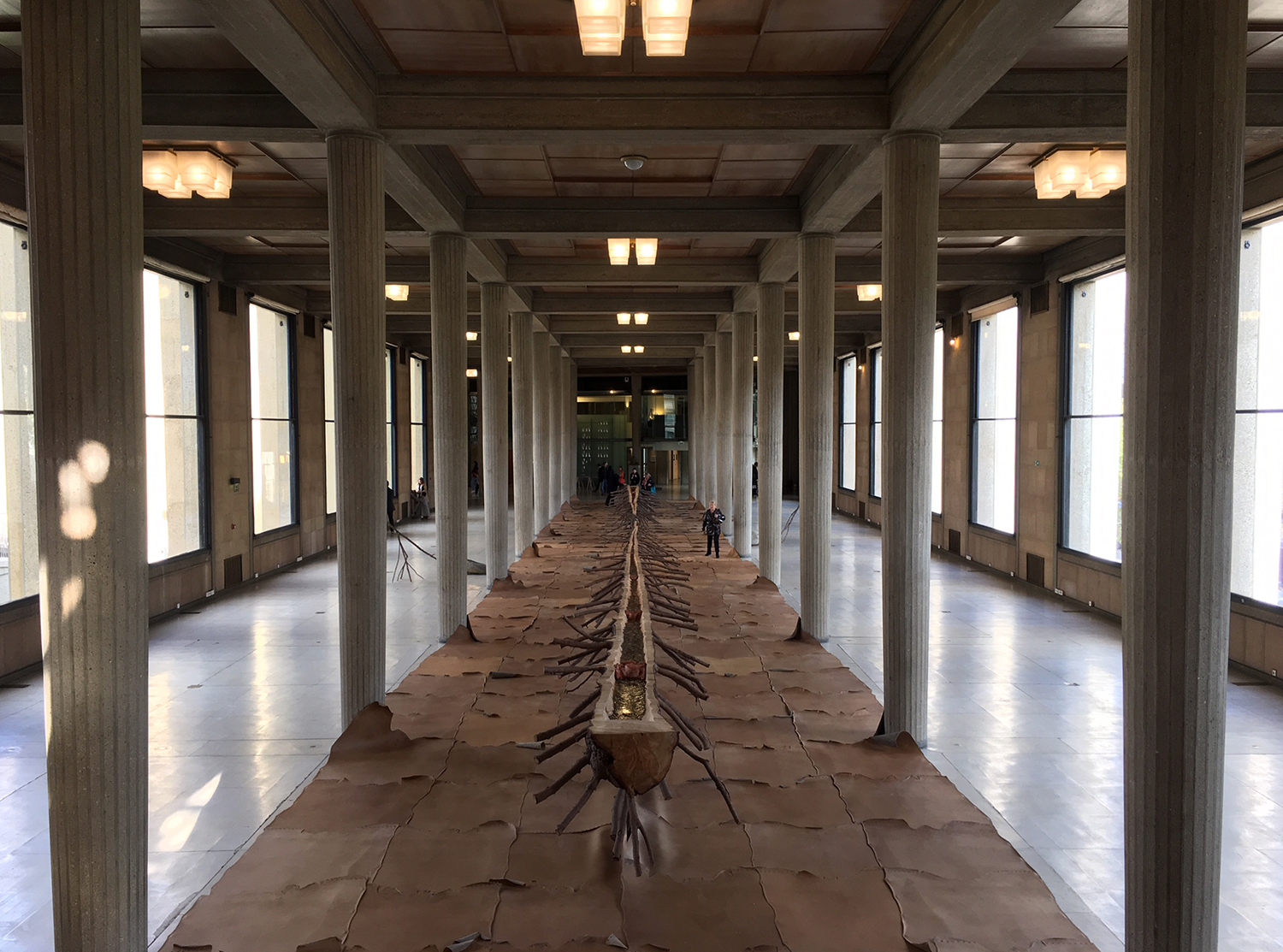 A room with columns, leather on the floor, and an art installation. There are people in the space.