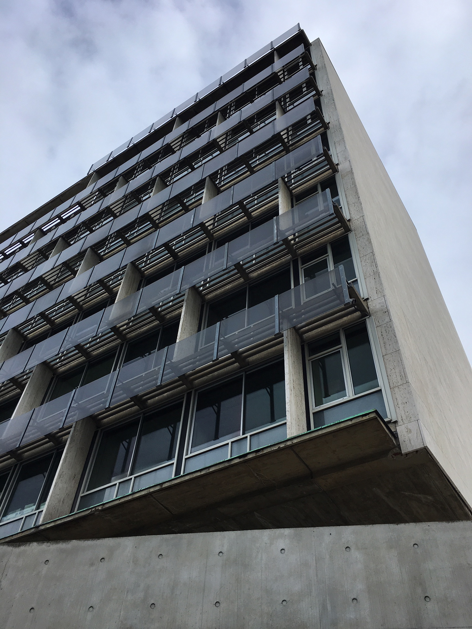 A corner of a building with windows and balconies with a concrete wall in the foreground.