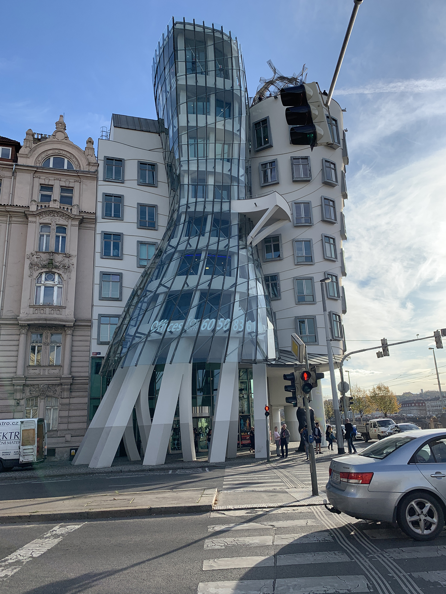 A uniquely shaped building. There are traffic lights, people, and cars in front of it.