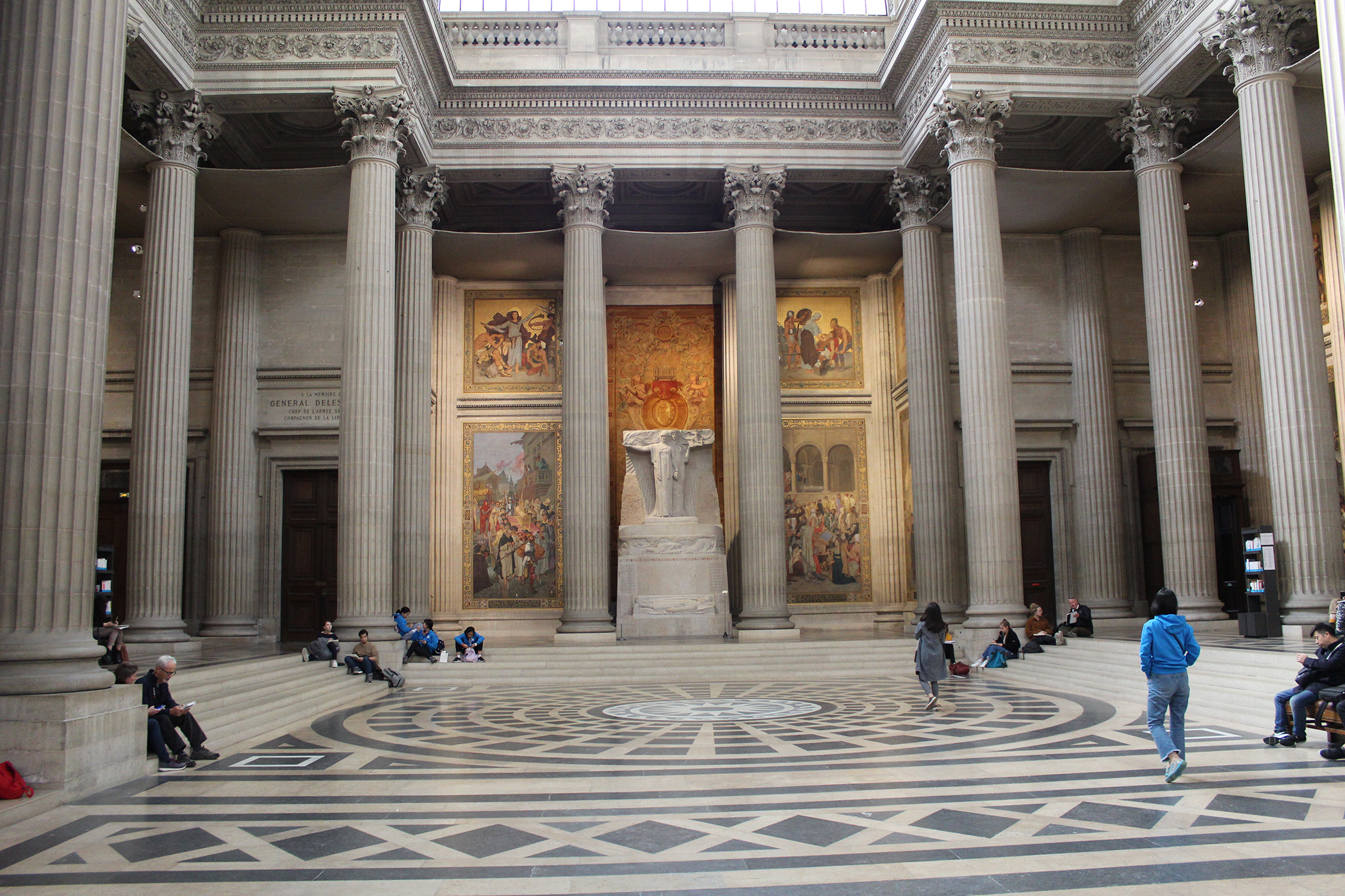 People walking, standing, and sitting in a open central area with stairs, columns, and a statue.