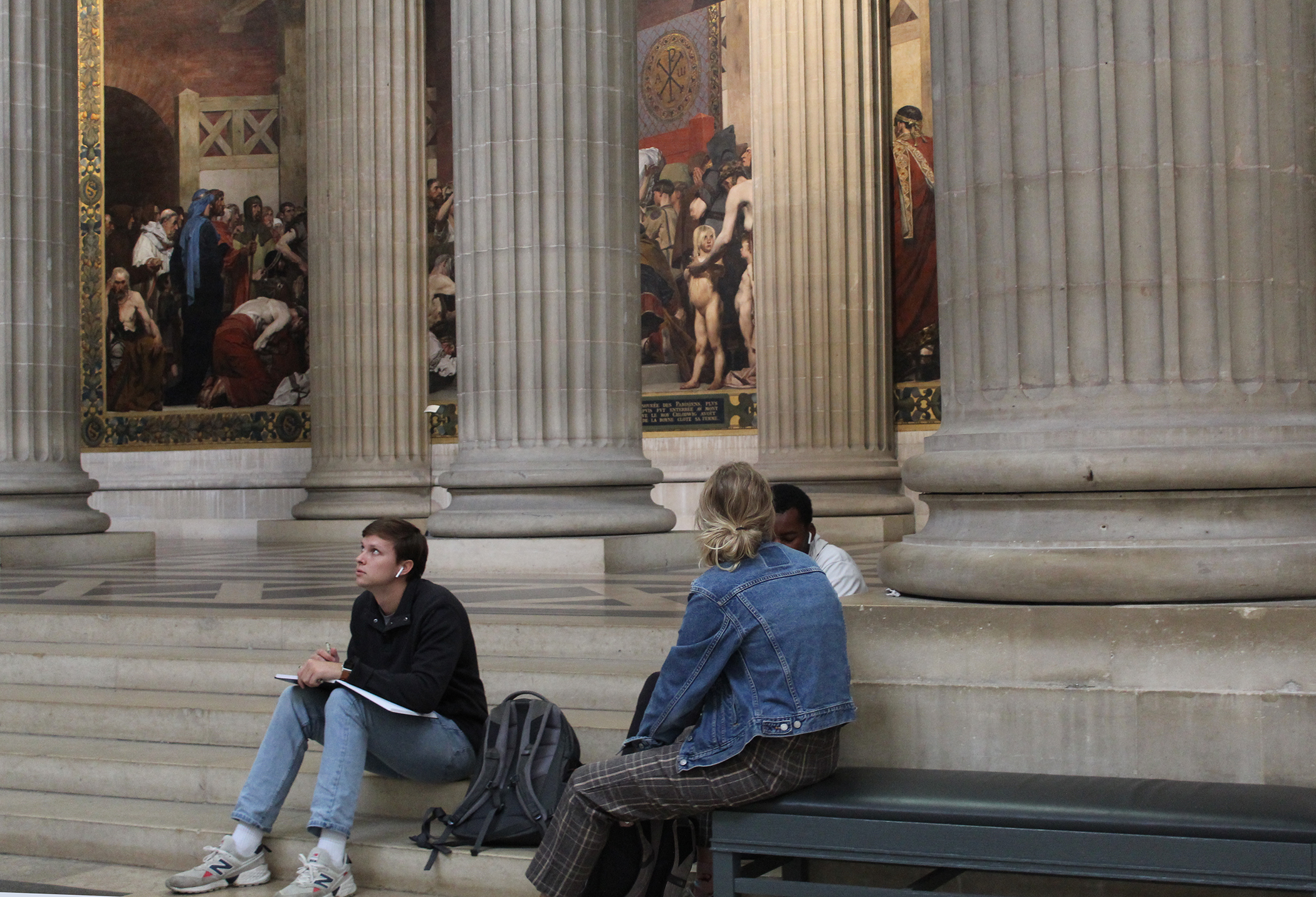 Three students sitting down in the Panthéon. One student is looking up.