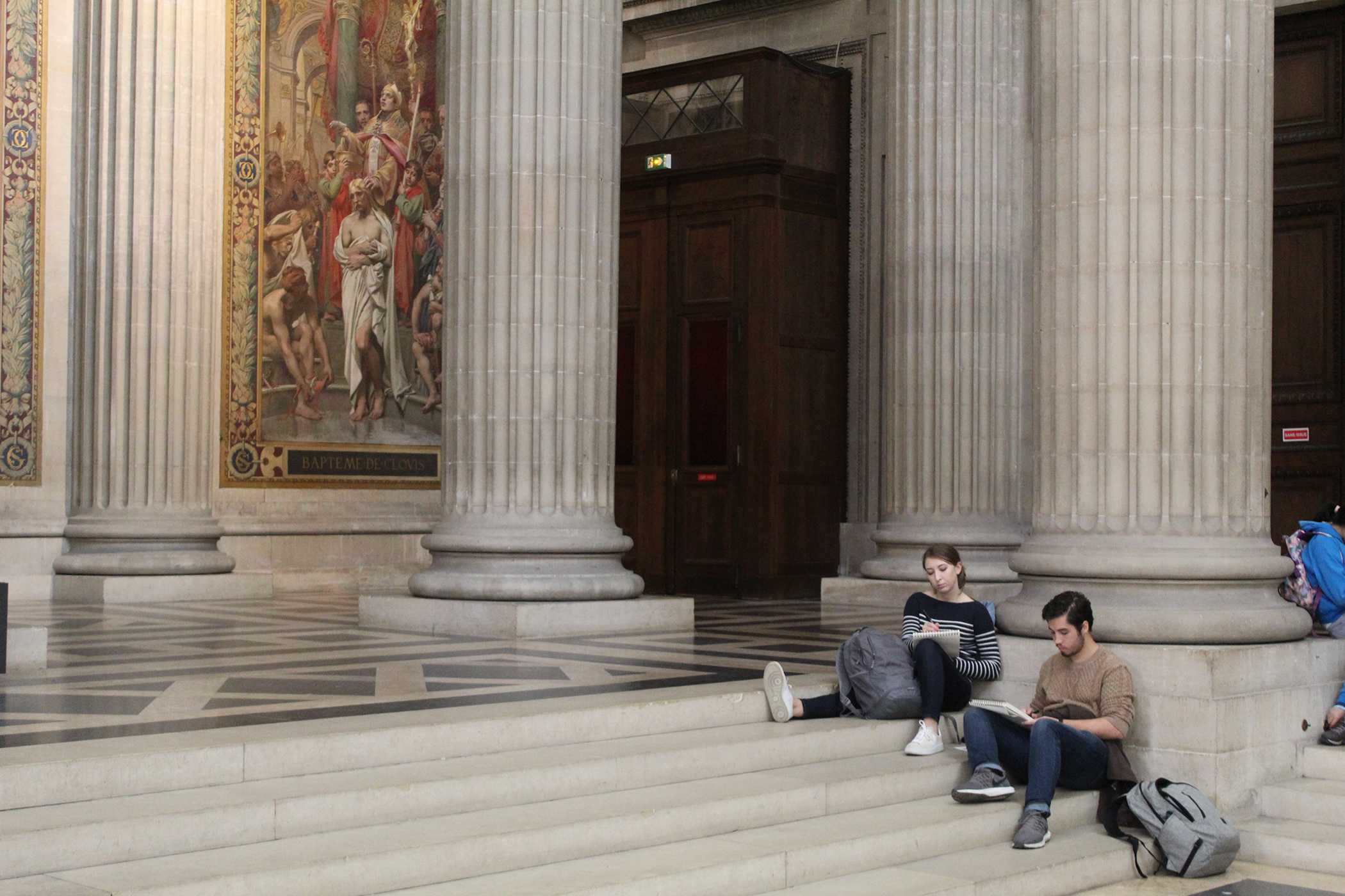 Two people sitting on the steps inside of the Panthéon looking into books they are holding.