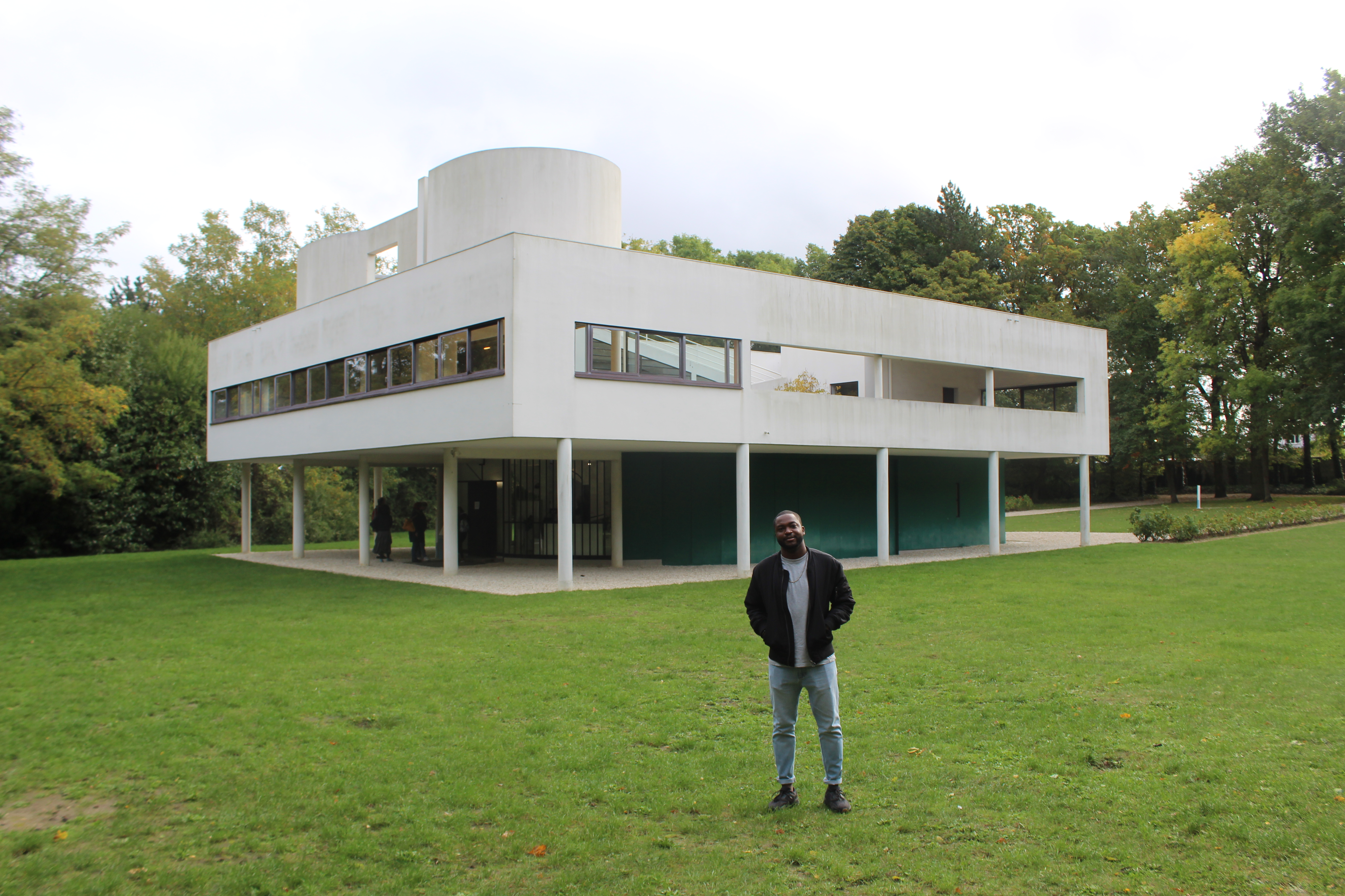 A person standing and posing in front of a building.