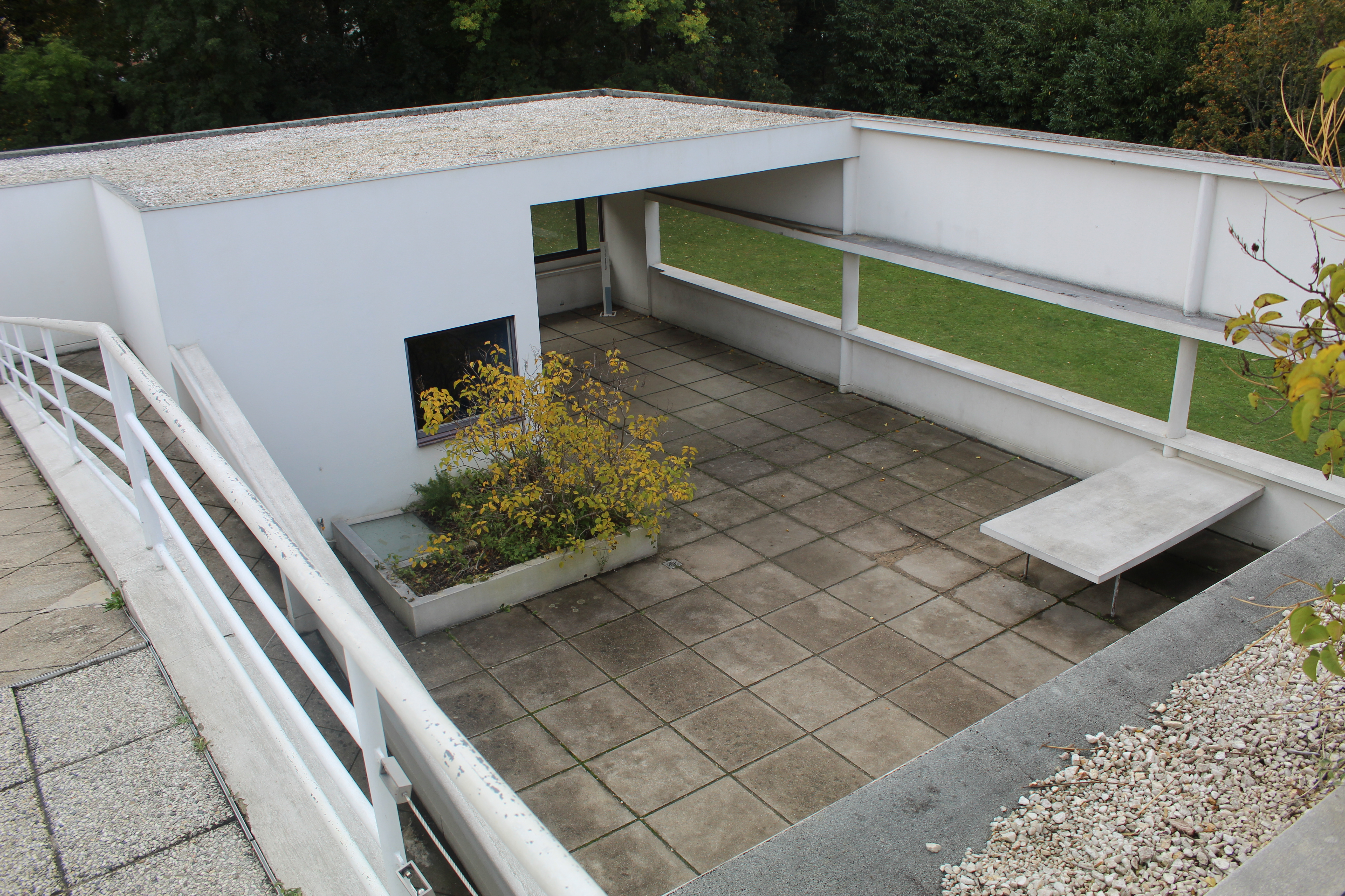Concrete rooftop with ramp and vegetation in planters.
