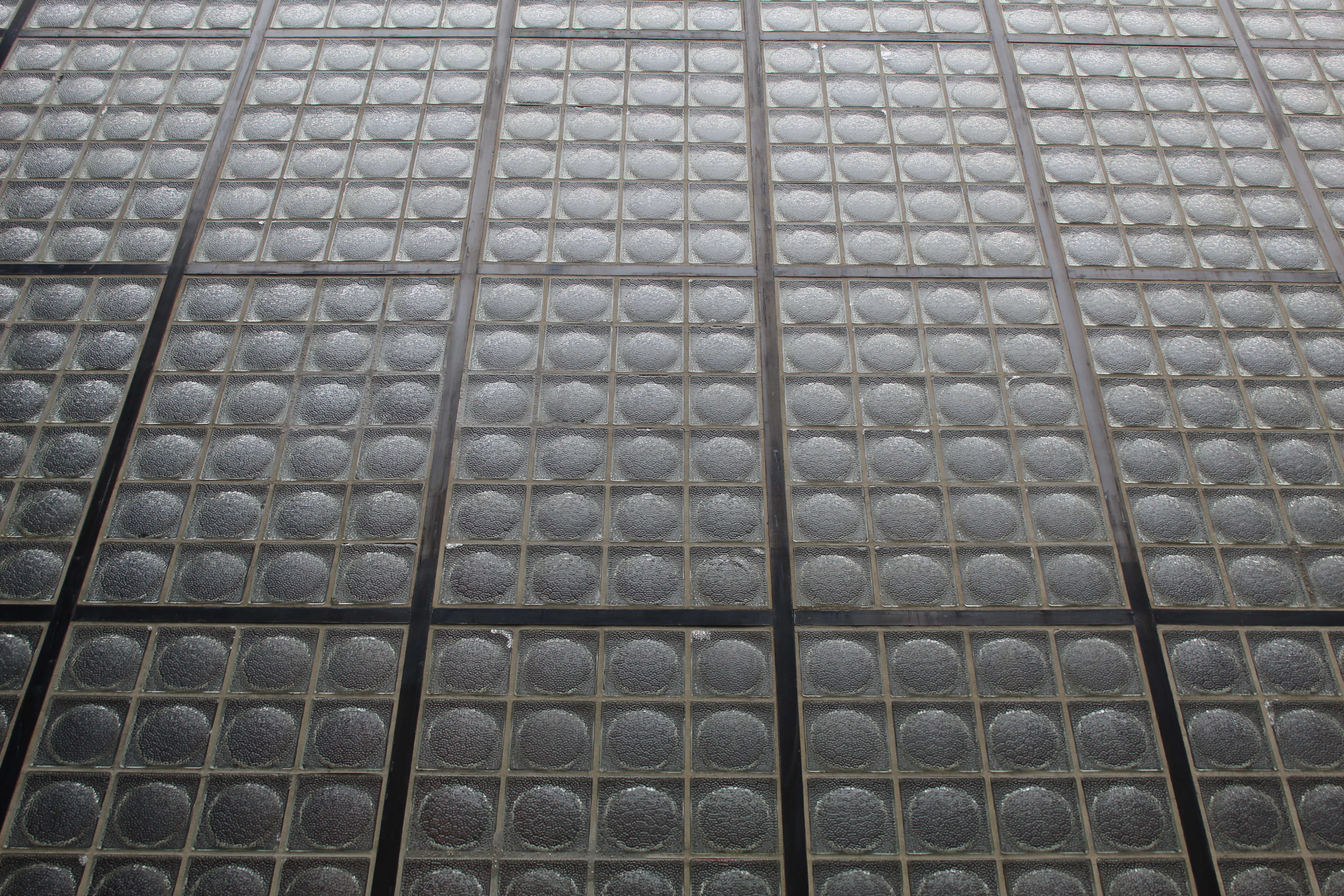 Square pieces of glass with a circular center in a steel frame.