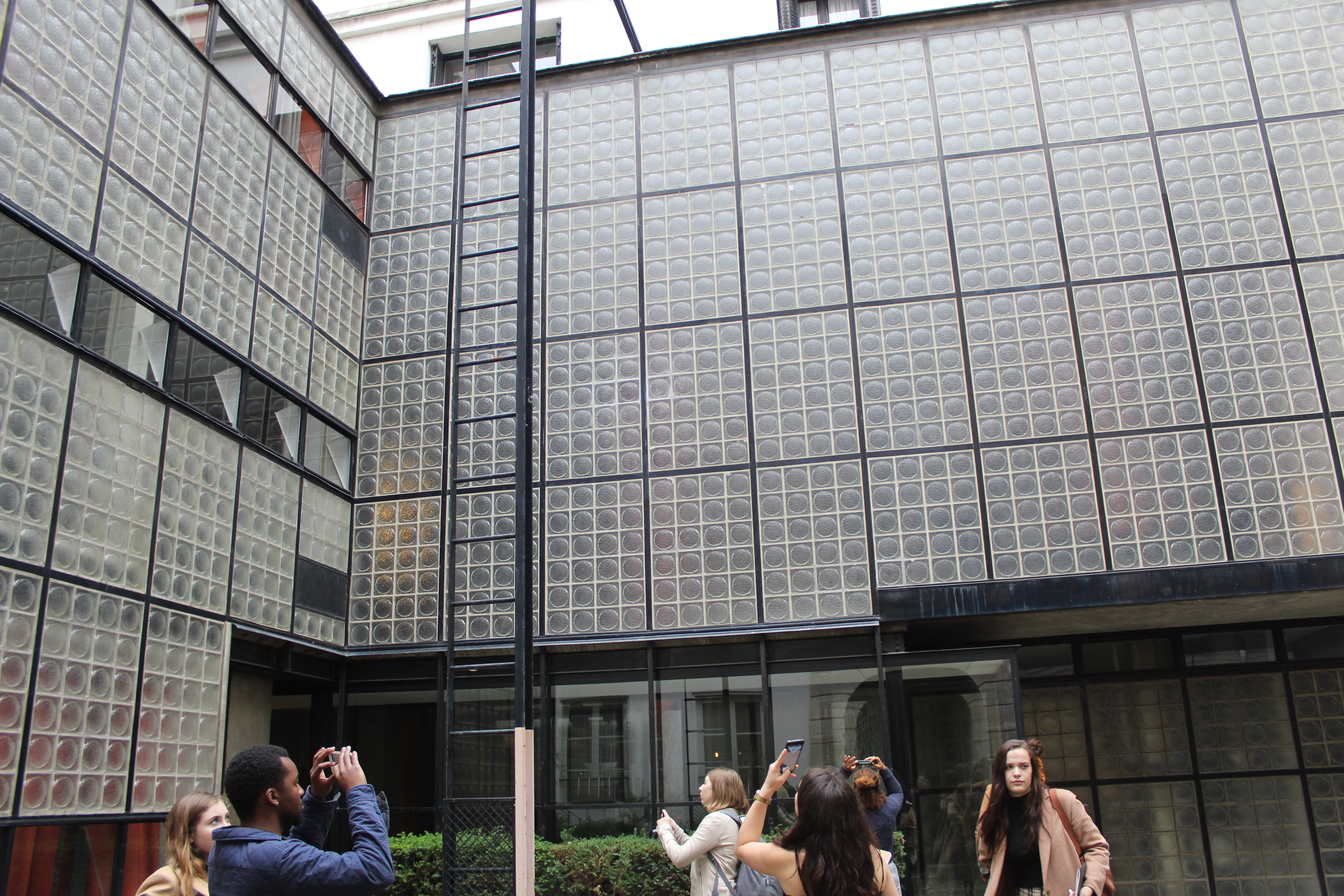 People standing and taking pictures in front of a building with black steel and many square windows.